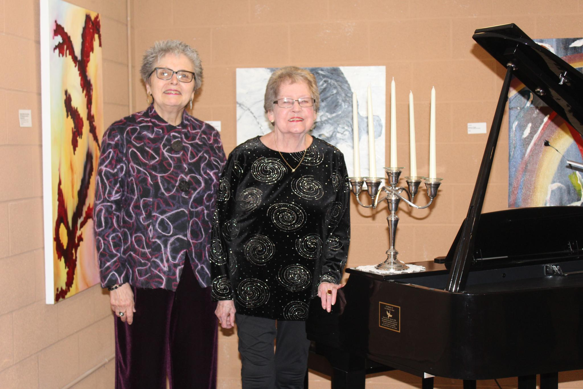 Joan Caruso and Lorna Penny with the grand piano they donated in the name of Dr. Robert R. Hesse