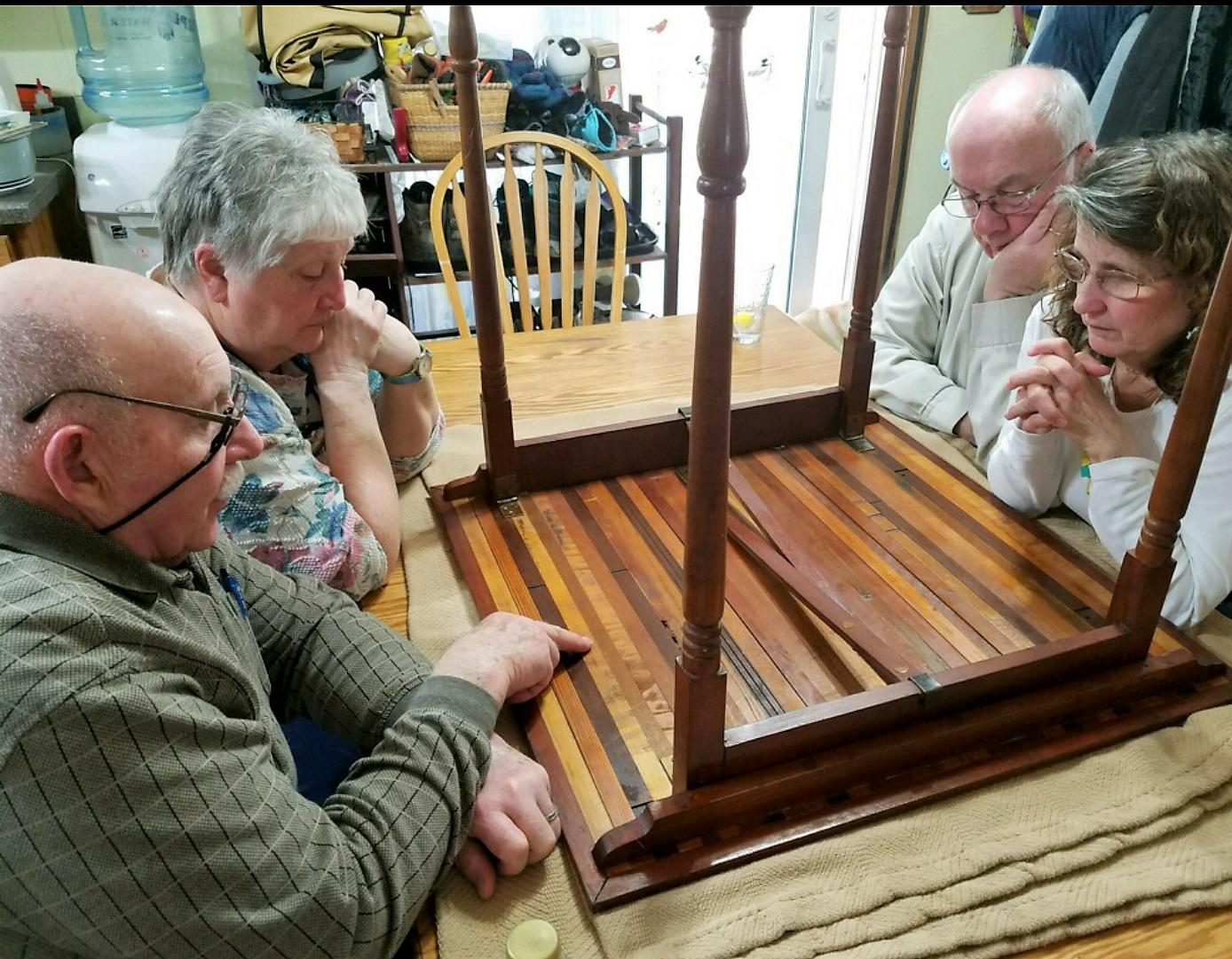This photo shows on left, Bonnie and Dick Lancaster, and on right George and Tracy Riedesel examining the bottom of the mystery table on April 1, 2018. Photo by Val Macer