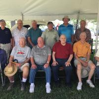 Group photo taken 7-8-18 at Ottaway Park: Back row left to right: Dave Turner (driver), Ron Blackmer (driver), Wally Howser (son of driver Jim Howser), John Swartout (son of original builder and owner of Coon Road Speedway, Joel Swartout), Skip Furlow (driver), Bill Catania (builder of #18 replica race car). Front row left to right: Emma Strain (widow of driver Don Strain), Ken See (driver), Al Brumagin (driver), Russ Weise (driver), Ray Sonnenberg (driver), Sean Hardy (current property owner of the site of